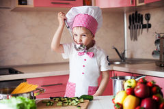 Portrait of little boy in the hat of the chef and an apron. Little cooks chef in the kitchen tasting the dish. Royalty Free Stock Photo