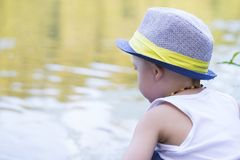 Portrait of a little  boy with a hat sitting next to the river. Portrait of a cute little boy with a hat, sitting by the river and enjoy the beautiful and sunny Royalty Free Stock Images