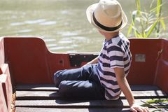 Portrait of a little  boy with a hat sitting next to the river. Portrait of a little sweet boy with a hat while sitting in a boat and enjoying a beautiful sunny Stock Photography