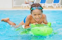 Boy having fun with inflatable toy in pool Royalty Free Stock Image