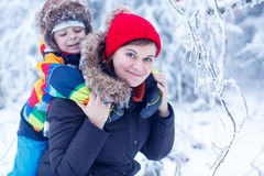 Portrait of a little boy and his mother in winter hat in snow fo Royalty Free Stock Photos