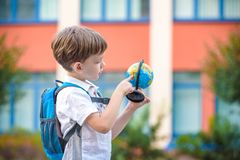 Portrait of a little boy holding a globe. Travel concept stock images