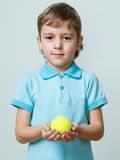 Portrait of a little boy holding tennis ball in the hands Stock Photo