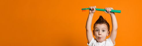 Portrait of a little boy holding a tooth brush over yellow background royalty free stock photo