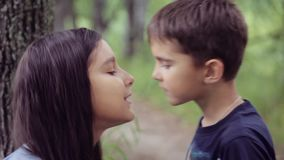 Portrait. A little boy is kissing with a little girl and hugging loving hard each other. Slow motion stock footage