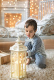 Portrait of little boy and a light in the room. Portrait of a Cute boy sits in pajamas looks on the candle in the lantern at Christmas Royalty Free Stock Images