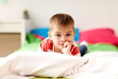 Portrait of little boy lying on bed at home Royalty Free Stock Photo