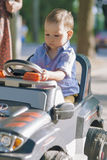 Portrait of Little Boy Managing to Drive a small car Royalty Free Stock Images