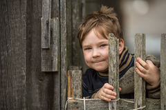 Portrait of little boy near a fence in the village. Happy. Stock Image