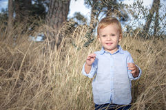 Portrait of a little boy  near withered grass Stock Image
