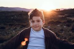 Little boy outdoors looking at the camera with serious expression. Kid in a sunset. Portrait of a little boy outside looking at the camera with serious stock photos