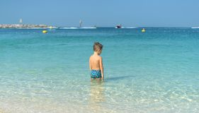 Portrait little boy playing in the sea, ocean. Happy family having fun on tropical white beach. Positive human emotions, feelings. Funny cute child making Royalty Free Stock Image
