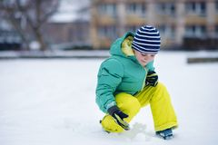 Portrait of little boy playing with snow in winter Stock Photo