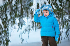 Portrait of a little boy playing in winter forest Stock Photos
