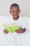 Portrait of a little boy reading book in bed Royalty Free Stock Photo