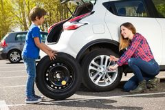 Little boy helping his mother to change flat tyre royalty free stock photos