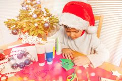 Little boy decorating paper Christmas tree royalty free stock photography