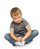 Portrait of little boy. Serious little boy in jeans and a gray shirt. The boy sits on the floor looking up to the sky - Isolated on white background Royalty Free Stock Images