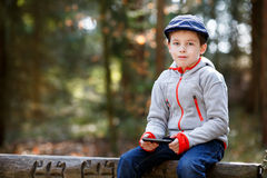 Portrait of little boy sitting on a bench outdoors Stock Images