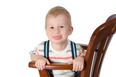 Portrait of little boy sitting on a chair Stock Image