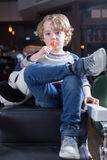 Portrait of little boy sitting in chair and eating lollipop. On a barber shop Royalty Free Stock Photos