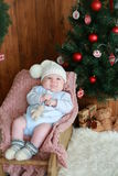 Portrait of a  little boy sitting on the  chair near Christmas tree Royalty Free Stock Photography