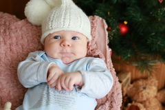 Portrait of a  little boy sitting on the  chair near Christmas tree Stock Photography