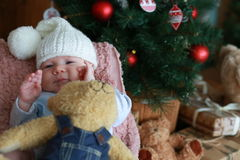 Portrait of a  little boy sitting on the  chair near Christmas tree Royalty Free Stock Image