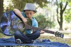 Portrait of a little boy sitting in a park and playing a guitar stock images