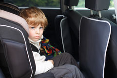 Portrait of little boy sitting in safety car seat Stock Photos
