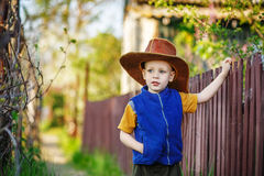 Portrait of a little boy standing in a big hat in the wooden fen Royalty Free Stock Images