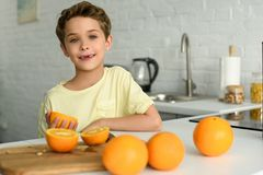 Portrait of little boy standing at counter with fresh oranges in kitchen. At home royalty free stock photo