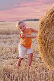 Portrait of little boy in a summer hat look out on a haystack in a field of wheat. stock image