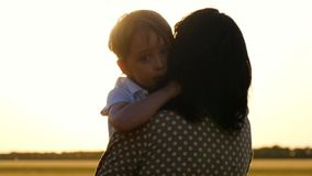 Portrait of a little boy. The sun`s rays touch the child`s face, embracing his mother and son experiencing emotions of. Happiness and pleasure. Slow motion stock video footage
