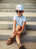 Portrait of little boy in sunglasses and hat sitting and laughin Stock Image