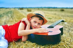Portrait of a little boy on vacation in the field . The child lying in the manger stock photos