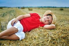 Portrait of a little boy on vacation in the field . The child lying in the manger royalty free stock photos