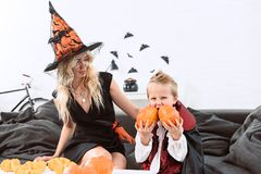 Portrait of little boy in vampire halloween costume biting pumpkins sitting on sofa with mother. In witch costume stock images