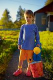 Portrait of little boy with watering can in garden at summer day Stock Photo