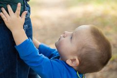 Portrait of a little boy wearing a blue jacket touching his mom on a sunny day stock photo