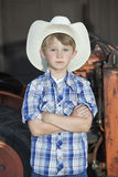 Portrait of a little boy wearing cowboy hat while standing with arms crossed against machine Stock Images