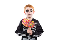 Portrait of little boy wearing halloween costume and holding colorful candies Royalty Free Stock Images
