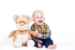 Portrait of a little boy on white background. Portrait of a smiling little boy with a plush toy, sitting on the floor in a bright room and isolated on a white Stock Image