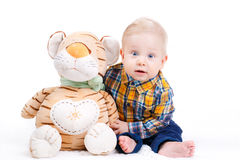 Portrait of a little boy on white background. Portrait of a smiling little boy with a plush toy, sitting on the floor in a bright room and isolated on a white Stock Photography