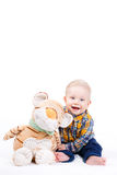 Portrait of a little boy on white background. Portrait of a smiling little boy with a plush toy, sitting on the floor in a bright room and isolated on a white Royalty Free Stock Photo