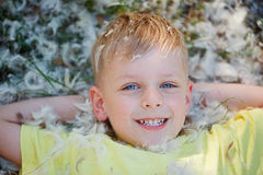 Portrait of a little boy who is lying on the grass covered with Royalty Free Stock Photography