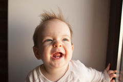 Portrait of a little boy who is sitting in the window and smiling. emotions concept. royalty free stock photography