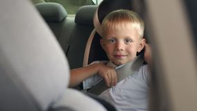 Portrait of a little boy 6 years old in a car seat, he is wearing seat belts. Slow motion. Child safety while traveling in the car stock video footage