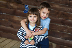Portrait of little brother hugging his little sister. Portrait of a cute little brother hugging his little sister. A wooden background Royalty Free Stock Photo