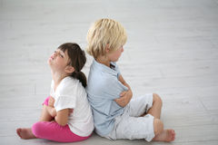 Portrait of little brother and sister offended after argue. Brother and sister sitting back to back on the floor Royalty Free Stock Images